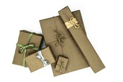 Mix of various sizes gift boxes wrapped in beige paper and bundled with different ribbons on white background.  stock photography