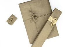 Mix of various sizes gift boxes wrapped in beige paper and bundled with different ribbons on white background.  royalty free stock photo