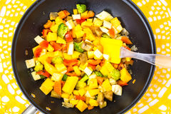 Mix vegetables, stewed in a pan  at home crocheted napkins on a Stock Image