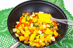 Mix vegetables, stewed in a pan  at home crocheted napkins on a Royalty Free Stock Images