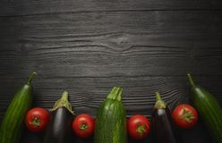 Mix zucchini tomato from fresh raw vegetables on a dark background close-up view from above. empty place. black wooden table stock photo