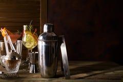 Mixbecher, swizzle, Zangen und Löffel mit Eis in einem Eimer für das Vorbereiten eines Sommercocktails auf dunklem Hintergrund mi Stockbild