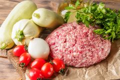 Mixe of ground meat minced beef and pork. Set for cooking barbecue steaks kebabs sausages fried on fire Food vegetables cherry tomatoes leaves lettuce parsley Stock Photos