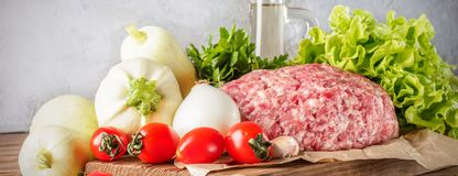 Mixe of ground meat minced beef and pork. Set for cooking barbecue steaks kebabs sausages fried on fire Food vegetables cherry tomatoes leaves lettuce parsley Stock Images