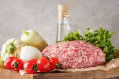 Mixe of ground meat minced beef and pork. Set for cooking barbecue steaks kebabs sausages fried on fire Food vegetables cherry tomatoes leaves lettuce parsley Stock Image