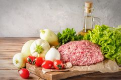 Mixe of ground meat minced beef and pork. Set for cooking barbecue steaks kebabs sausages fried on fire Food vegetables cherry tomatoes leaves lettuce parsley Royalty Free Stock Image