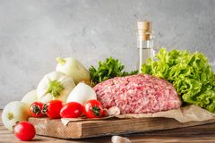 Mixe of ground meat minced beef and pork. Set for cooking barbecue steaks kebabs sausages fried on fire Food vegetables cherry tomatoes leaves lettuce parsley Royalty Free Stock Photos