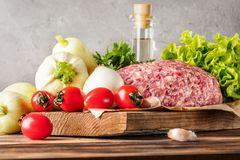 Mixe of ground meat minced beef and pork. Set for cooking barbecue steaks kebabs sausages fried on fire Food vegetables cherry tomatoes leaves lettuce parsley Royalty Free Stock Photo