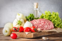 Mixe of ground meat minced beef and pork. Set for cooking barbecue steaks kebabs sausages fried on fire Food vegetables cherry tomatoes leaves lettuce parsley Stock Photography