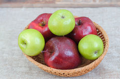 Mixed apples in basket on the table Stock Photos