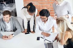 Mixed arced team trying to achieve good results in business stock photography