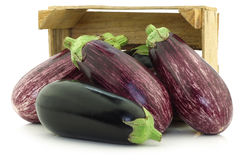 Mixed aubergines in a wooden crate Stock Photos