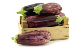 Mixed aubergines in a wooden crate Stock Image