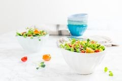 Mixed baby greens and cherry tomatoes salad in bowl. Superfood s stock photo