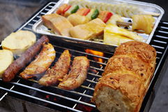 Mixed barbecue grill. Poultry, fish, bread and cheese beeing broiled on the barbecue grill Royalty Free Stock Photo
