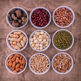 Mixed beans , lentils and nuts in the white bowl on brown cloth Royalty Free Stock Image