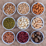Mixed beans , lentils and nuts in the white bowl on brown cloth Stock Images