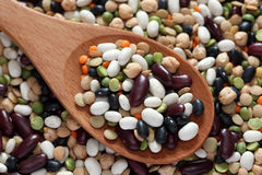 Mixed beans in a wooden spoon. On mixed beans background. Close-up Royalty Free Stock Photos