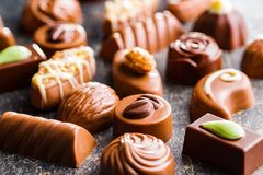 Mixed belgian pralines. Chocolate truffles. Mixed belgian pralines. Chocolate truffles on old kitchen table stock photo