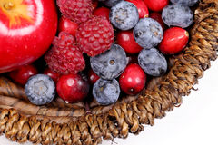 Mixed berries. In a basket on green wooden background royalty free stock image