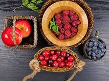 Mixed berries. In a basket on green wooden background Royalty Free Stock Images