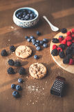 Mixed berries, blueberry, raspberry. On the kitchen, cooking with forest berries,  chocolate, biscuits, and cookies. On the table, waiting for breakfest Royalty Free Stock Photography