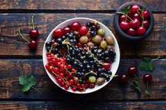 Mixed Berries in a Bowl. Fresh berries and cherries in a bowl, on wooden vintage background Royalty Free Stock Images