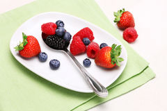 Mixed Berries Fruits. A plate of mixed berries, blueberries, strawberry, raspberry and black berries on table setting stock photo