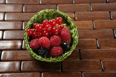 Mixed berries in a green little basket. Mixed forest berries dessert in a green little basket stock image