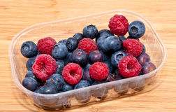 Mixed berries in plastic box Royalty Free Stock Images
