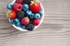 Mixed berries in plate on rustic wooden background. Stock Image