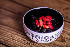Mixed berries in plate on rustic wooden background. Close up, top view, high resolution product. Harvest Concept. Top. Mixed berries in plate on rustic wooden Stock Photo