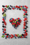 Mixed berries shaped as a heart and frame Stock Photo