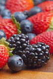 Mixed berries on wooden background with selected focus Stock Photography