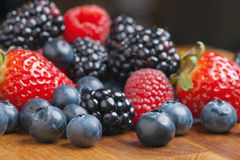 Mixed berries on wooden background with selected focus Stock Photos