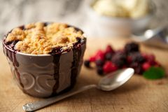 Mixed Berry Crumble Dessert with Ice-Cream in the Background Royalty Free Stock Photos