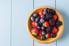 Mixed Berry Fruits in Wooden Bowl on Light Blue Wood Planked Tab Stock Image