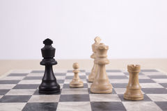 Mixed black and white wooden chesspieces on chessboard Stock Images