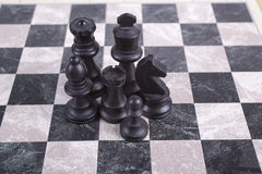 Mixed black wooden chesspieces on chessboard. Mixed black wooden chesspieces standing on chessboard Royalty Free Stock Images