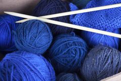 Mixed blue knitting yarn in a box with needles. Skeins of mixed blue knitting yarn in a box with needles Stock Photography
