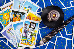 Mixed blue tarot cards with magic ball and candle. Many mixed blue tarot cards on the table with a crystal ball, magic wand and black candle Royalty Free Stock Photography