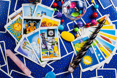 Mixed blue tarot cards with a magic ball and wand. Many mixed blue tarot cards on the table with a crystal ball, magic wand and other magic items Royalty Free Stock Image