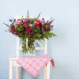 Mixed bouquet flowers on chair Stock Images