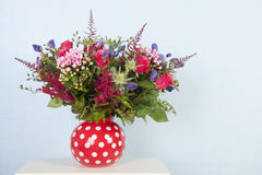 Mixed bouquet flowers. Red dotted vase with mixed bouquet flowers on blue background stock photo