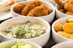 Mixed brazilian snacks, including pastries, fried chicken, salad Stock Photography
