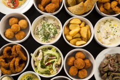 Mixed brazilian snacks, including pastries, fried chicken, salad Royalty Free Stock Images