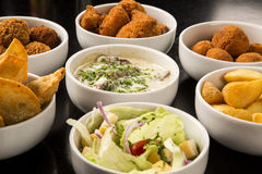 Mixed brazilian snacks, including pastries, fried chicken, salad Royalty Free Stock Photo