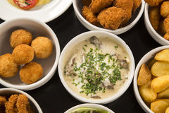 Mixed brazilian snacks, including pastries, fried chicken, salad Stock Photo