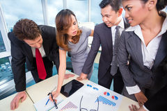 Mixed business team discussing earnings Stock Image