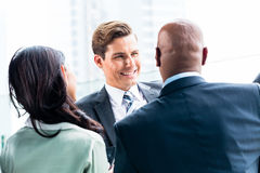 Mixed business team discussing outdoors Stock Image